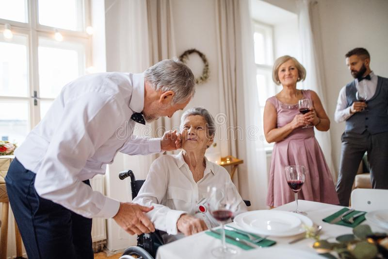 En äldre farmor i en rullstol som firar födelsedagen med familjen, partibegrepp arkivfoton
