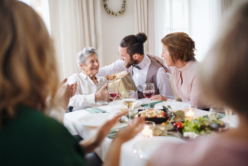 En äldre farmor som firar födelsedag med familjen och mottar en gåva, partibegrepp fotografering för bildbyråer