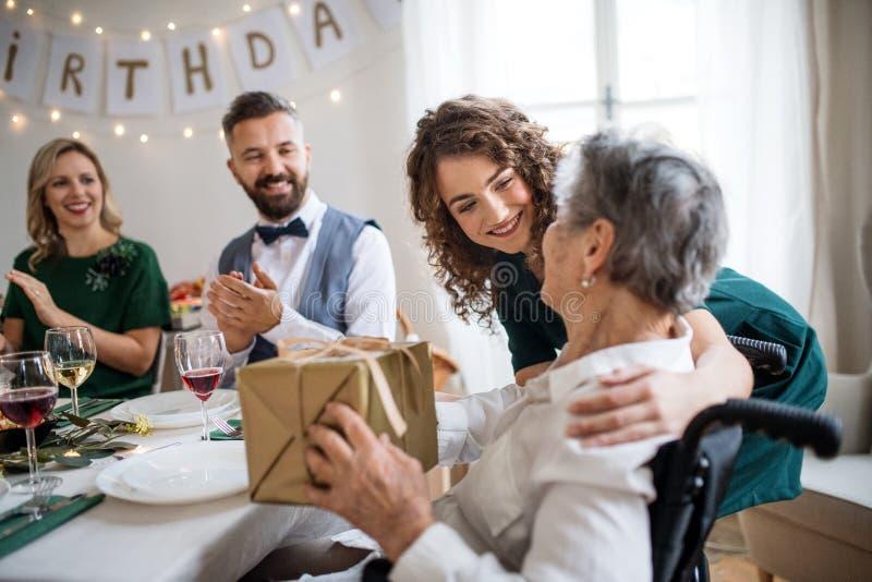 En äldre farmor som firar födelsedag med familjen och mottar en gåva, partibegrepp royaltyfri foto