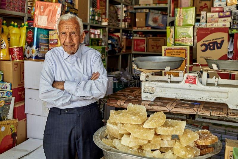 En äldre iransk specerihandlare står på ingången till matlagret royaltyfri foto