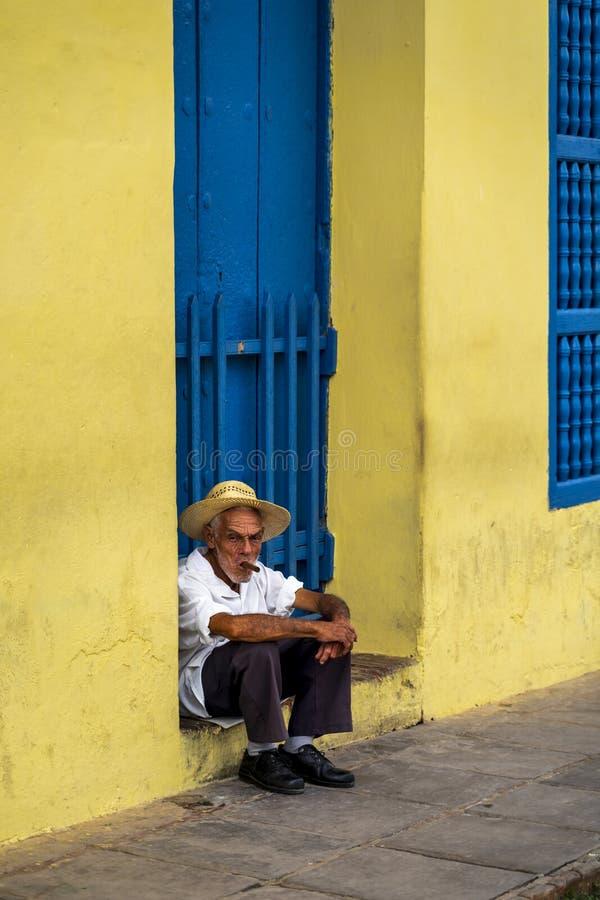 En äldre kuban som sitter på en tröskel som röker en cigarr royaltyfri bild