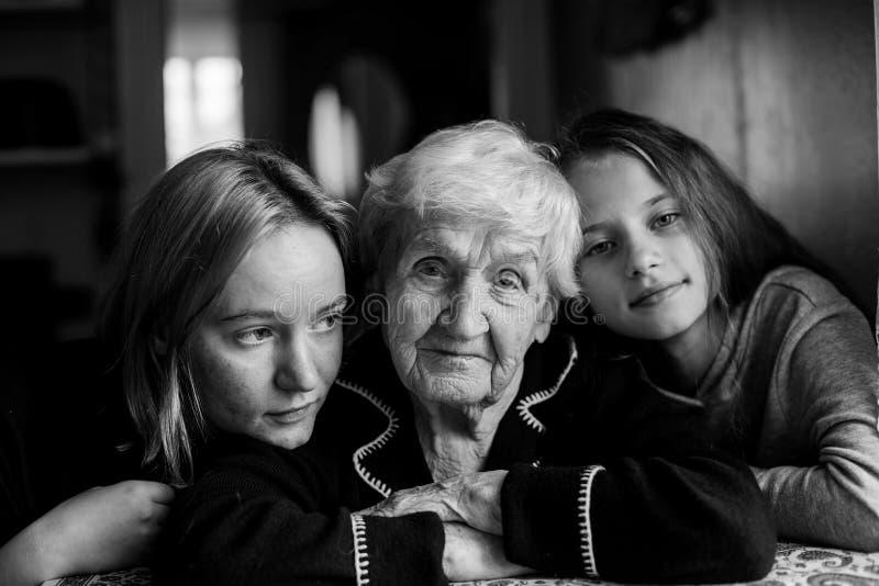En äldre kvinna fotograferas med två sondöttrar royaltyfri bild