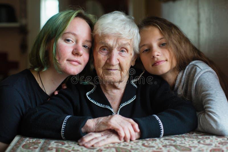 En äldre kvinna fotograferas med två sondöttrar royaltyfria foton