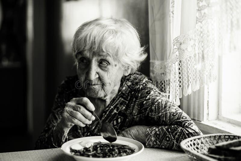 En äldre kvinna har lunch hemma arkivfoto
