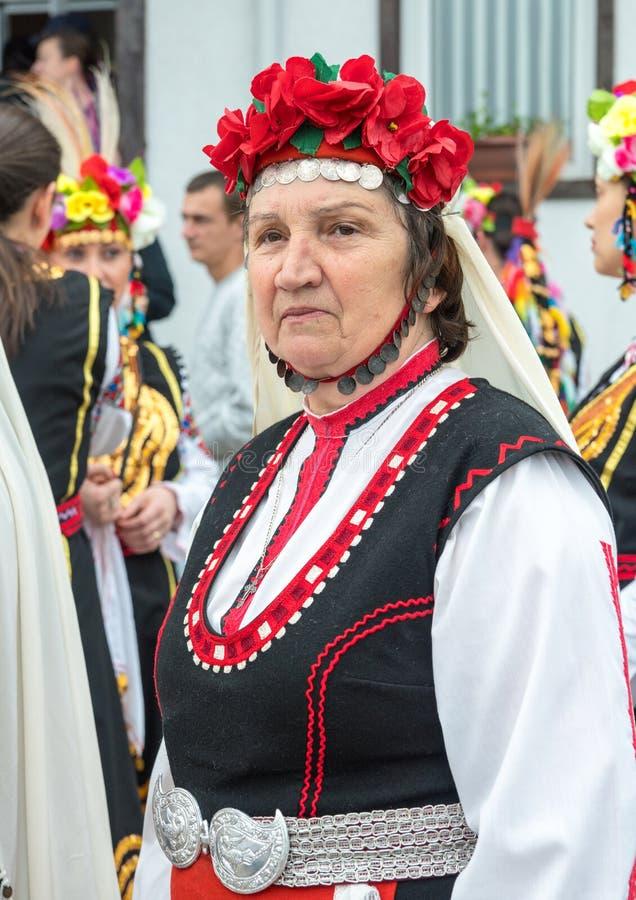 En äldre kvinna i en nationell bulgarisk dräkt på Nestenkaren spelar, Bulgarien royaltyfri bild