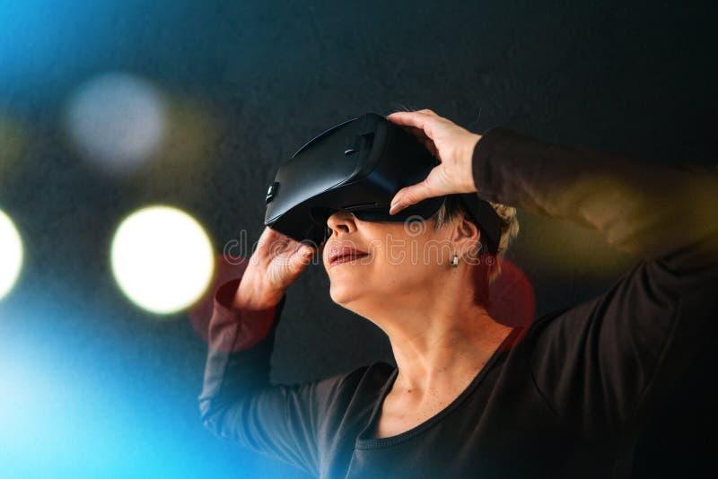 En äldre kvinna i virtuell verklighetexponeringsglas En äldre person som använder modern teknologi arkivfoto