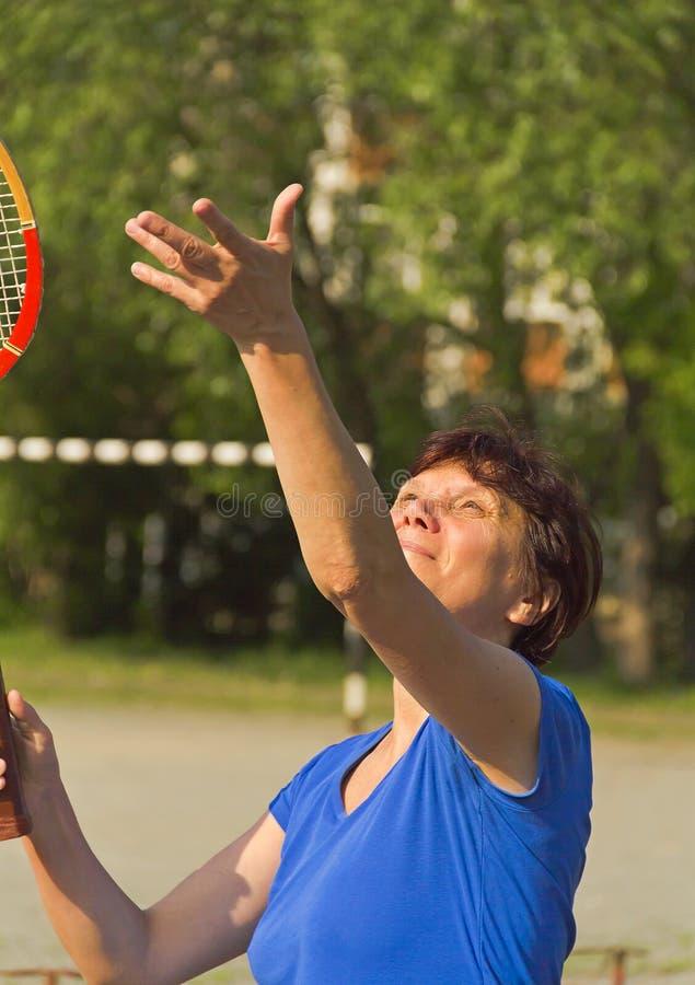 En äldre kvinna med en racket fångar en tennisboll arkivbild