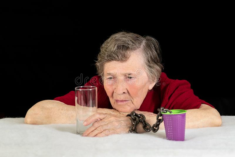 En äldre kvinna med gråa hårblickar longingly på glasföremålet Kvinnans hand kedjas fast till en plast- kopp som ett begrepp av arkivbild