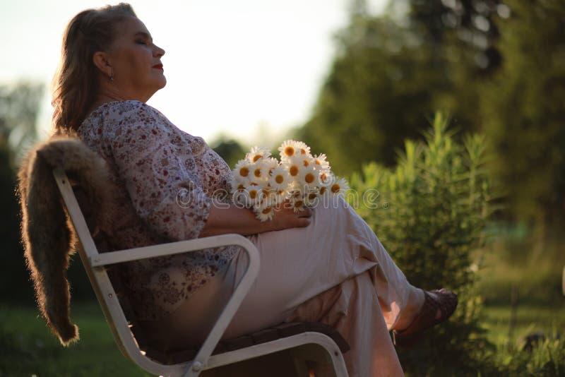 En äldre kvinna på farstubron av ett hus arkivfoto