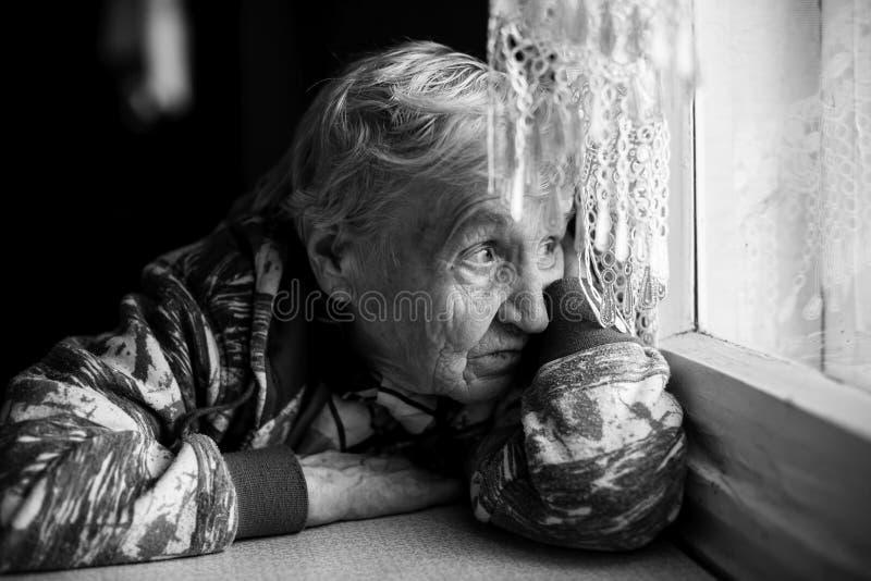 En äldre kvinna ser tankfullt och litet sorgset ut fönstret arkivbild