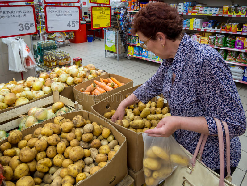 En äldre kvinna väljer potatisar i en packe arkivfoto