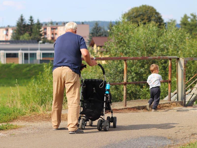 En äldre man går med hans sonson på naturen som framme skjuter en behandla som ett barnsittvagn av honom Familjen vilar i natur O royaltyfria foton