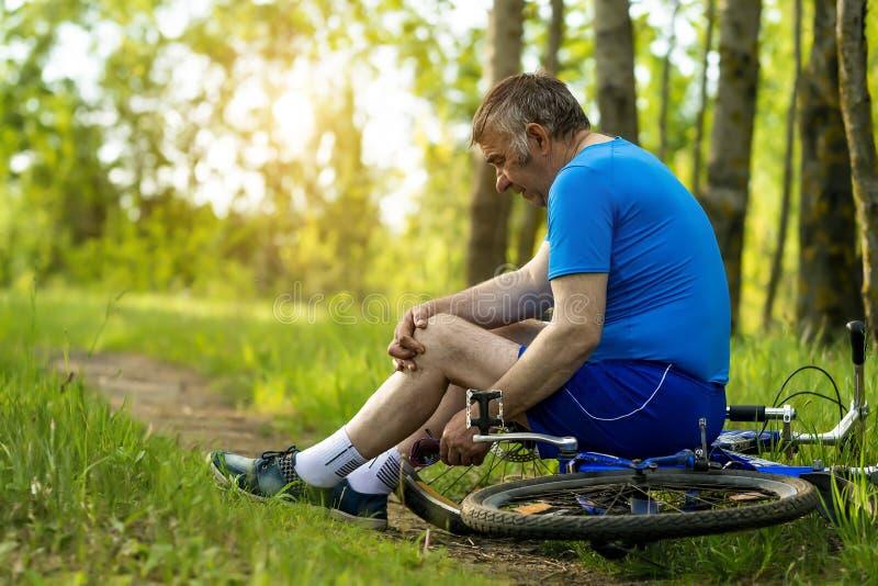 En ?ldre man g?r ont hans ben, medan rida en cykel royaltyfri fotografi