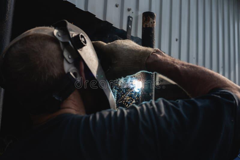En äldre man i arbeten för en skyddande maskering med elektrisk svetsning Hantverkare som är förlovad i hem- reparation arkivfoton