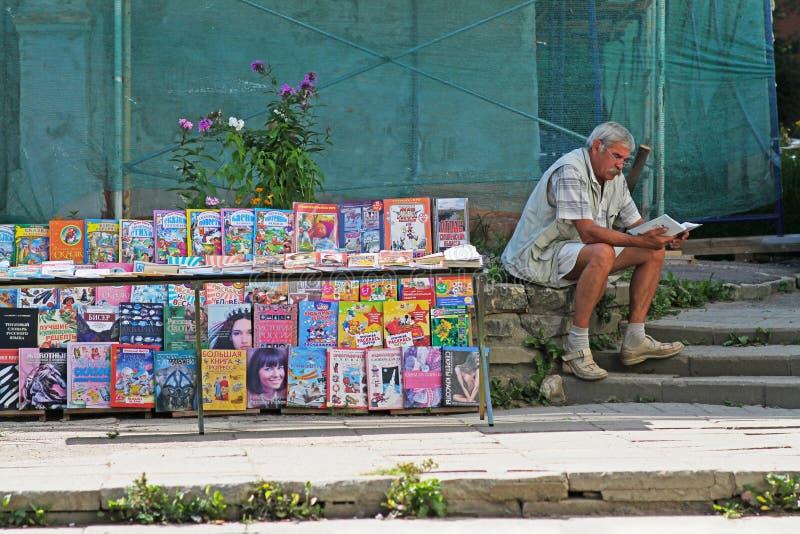 En äldre man i exponeringsglas som läser en bok på en gataförsäljning i Smolensk royaltyfri foto