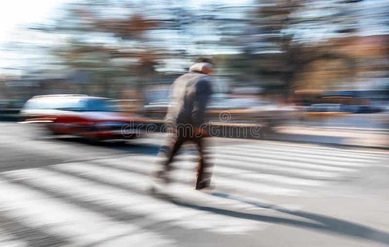 En äldre man korsar gatan i en övergångsställe arkivbild