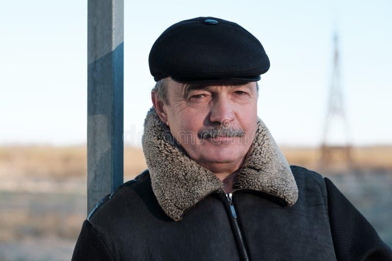 En äldre man med en mustasch bär ett lock arkivbilder