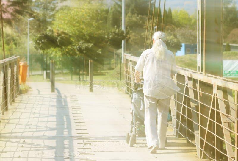 En äldre man med långt, grått idrotts- byggandehår går med ett barn i en pram över en bro Aktivitet i gamling Kurser för royaltyfri foto