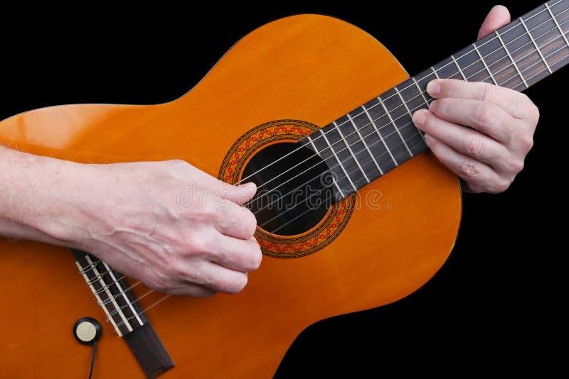 En äldre man med nervösa händer spelar en klassisk gitarr retro M royaltyfria foton