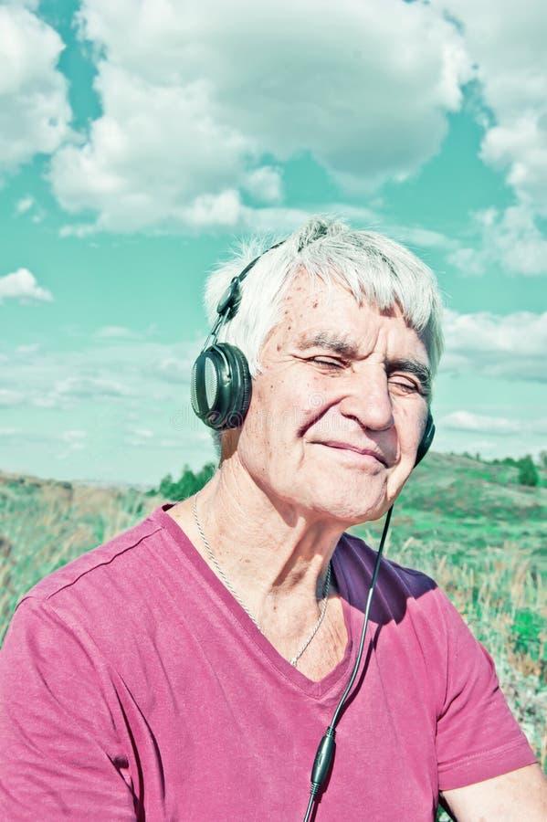En äldre man med stängda ögon i hörlurar lyssnar till det musik tonade fotoet Åldring som ler mannen som sitter utomhus- under-mo royaltyfri fotografi