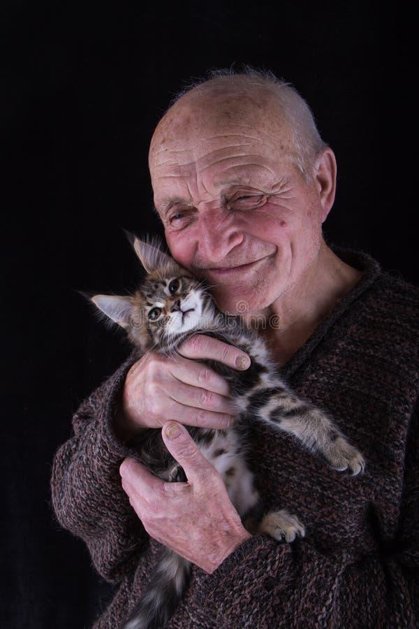 En ?ldre man rymmer den Maine Coon kattungen till hans framsida och leenden, en svart bakgrund, selektiv fokus royaltyfria bilder