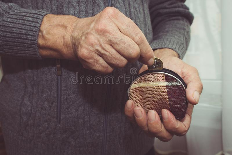 En äldre man sätter ett mynt i en tom plånbok armod royaltyfri fotografi