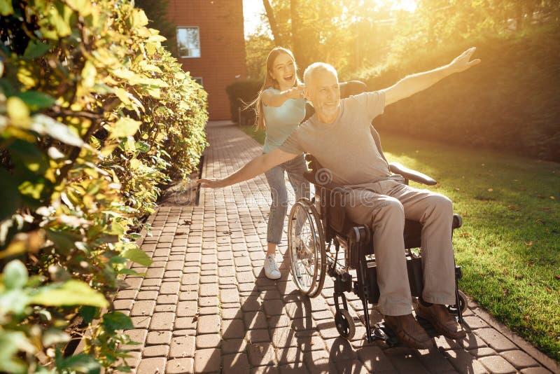 En äldre man sitter i en rullstol Flickan rullar det, och de bedrar omkring De går utanför och skrattar royaltyfria bilder