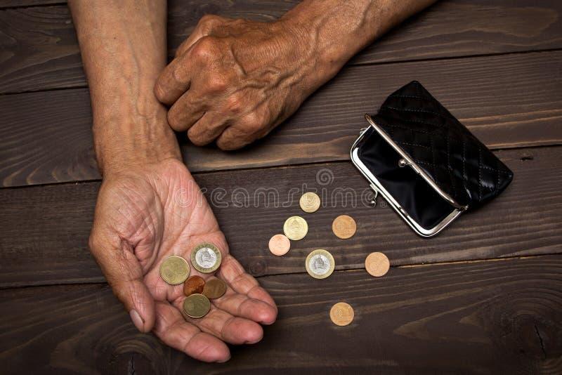En äldre man som rymmer en gammal mynthandväska och mynt Begreppet av armod i avgång arkivfoto