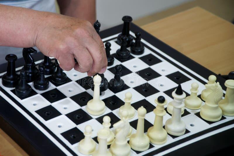 En äldre man spelar schack Special uppsättning av diagram för rullgardinen eller handelsresanden royaltyfria bilder