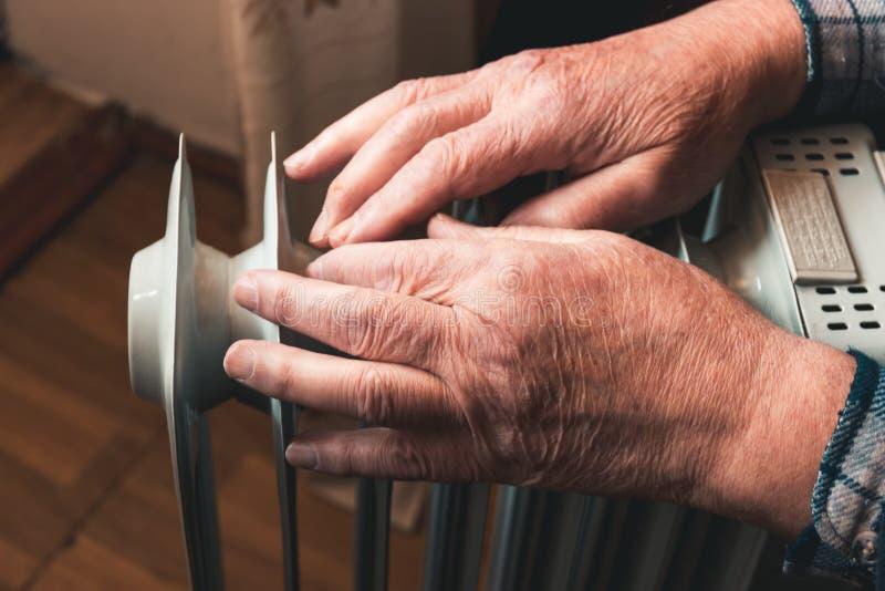 En äldre man värme hans händer över ett värmeelement I det lågsäsongt försenas centralvärme, så folket måste köpa royaltyfria foton