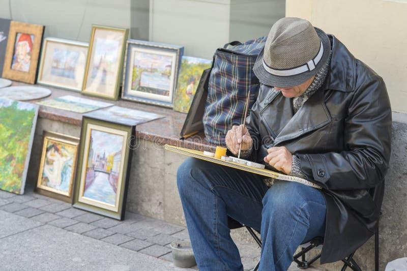 En äldre manlig konstnär målar en bild på den Nevsky utsikten St Petersburg, Ryssland, September, 2018 royaltyfria foton