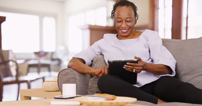 En äldre svart kvinna använder hennes minnestavla, medan koppla av på soffan arkivfoton