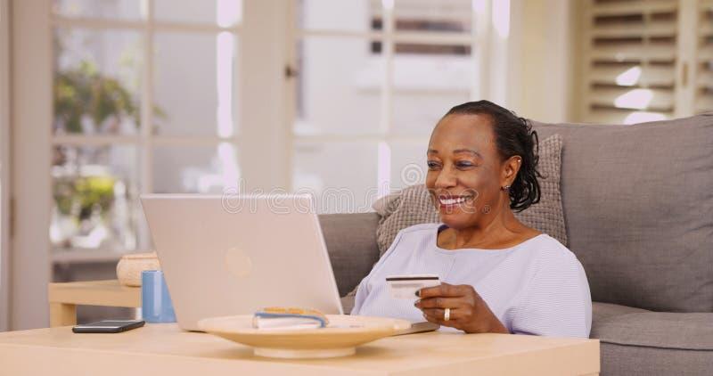 En äldre svart kvinna betalar hennes räkningar på hennes bärbar dator arkivfoto
