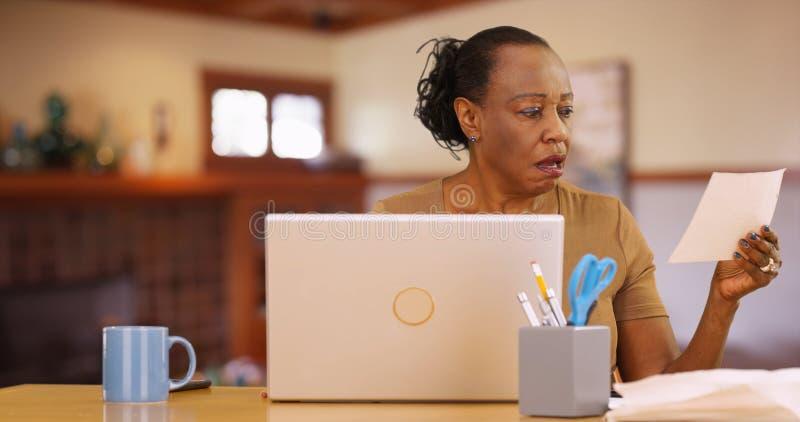 En äldre svart kvinna som framme sitter av datoren som är chockad vid räkningbetalningar arkivfoton