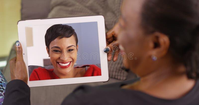 En äldre svart kvinna som talar till hennes dotter via video pratstund arkivbild