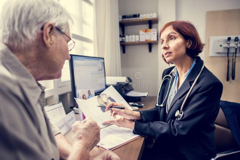 En äldre tålmodig mötedoktor på sjukhuset arkivfoto