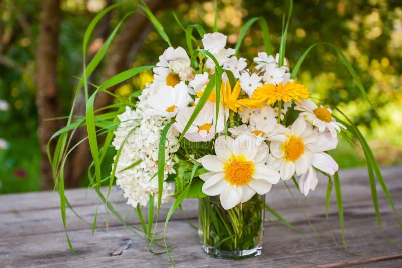 En älskvärd bukett med vita blommor och gröna blad på en trätabell i trädgården royaltyfri foto