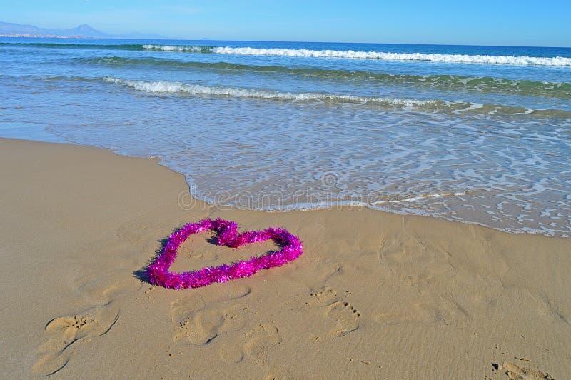En älskvärd hjärta formad julgarnering på stranden arkivfoton