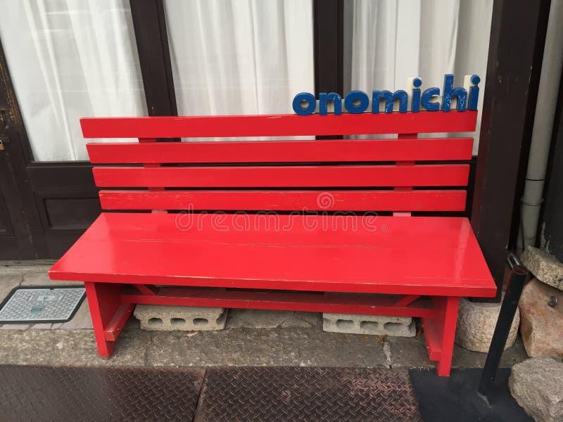 En älskvärd röd stol med Onomichi wordings utanför en shoppa av shoppinggatan royaltyfri bild