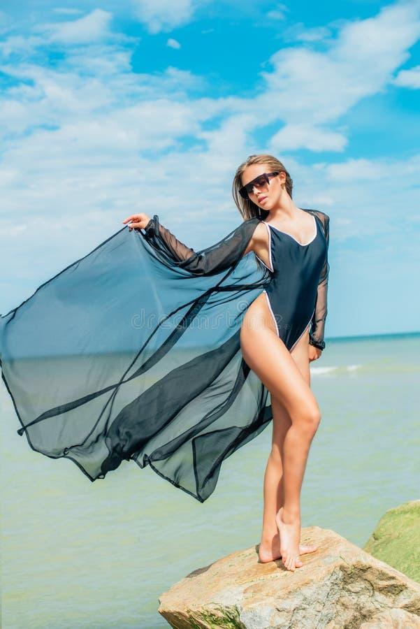 En älskvärd ung flicka med en ideal kropp i en baddräkt och en genomskinlig udde på en sommar sätter på land fotografering för bildbyråer