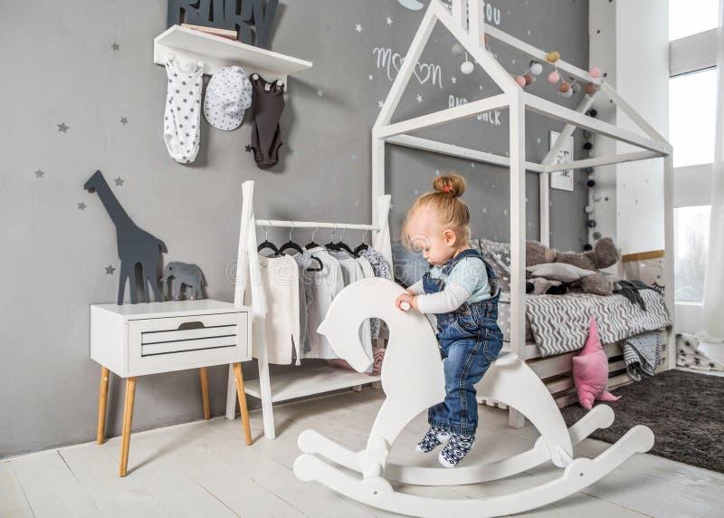 En-år-gammal flicka som nära spelar i rummet med en leksakhäst, ska royaltyfri foto