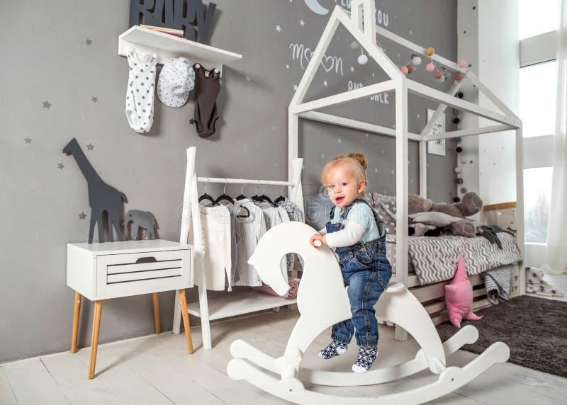 En årig flicka som nära spelar i rummet med en leksakhäst, ska arkivbild