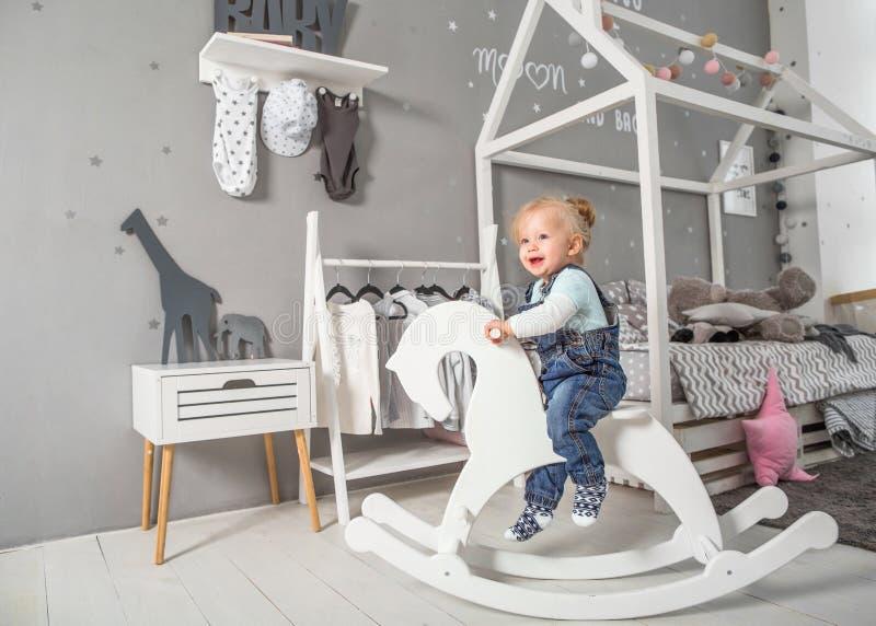 En årig flicka som nära spelar i rummet med en leksakhäst, ska fotografering för bildbyråer