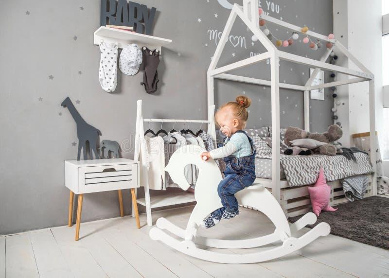 En årig flicka som nära spelar i rummet med en leksakhäst, ska royaltyfria foton