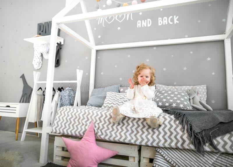 En årig flicka som nära spelar i rummet med en leksakhäst, ska royaltyfri bild