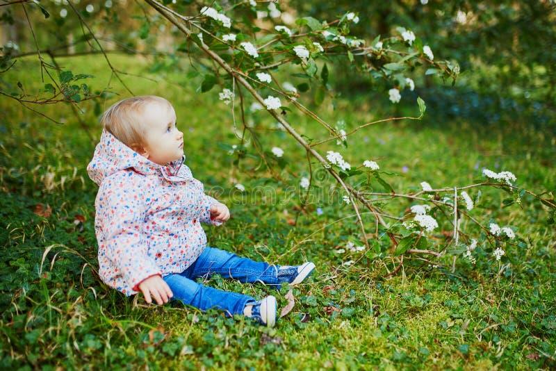 En årig flicka som sitter på gräset under trädfilial royaltyfri bild