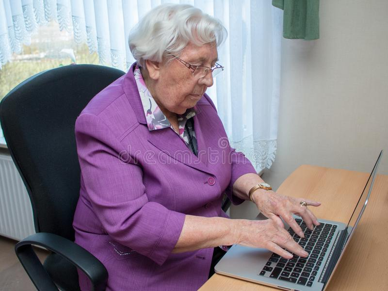 En 95-årig kvinna skriver på ett bärbar datortangentbord fotografering för bildbyråer
