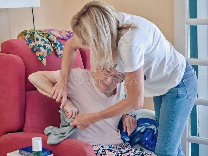 En 83-årig pensionär i hennes vingstol och den geriatriska sjuksköterskan hjälper henne arkivbilder