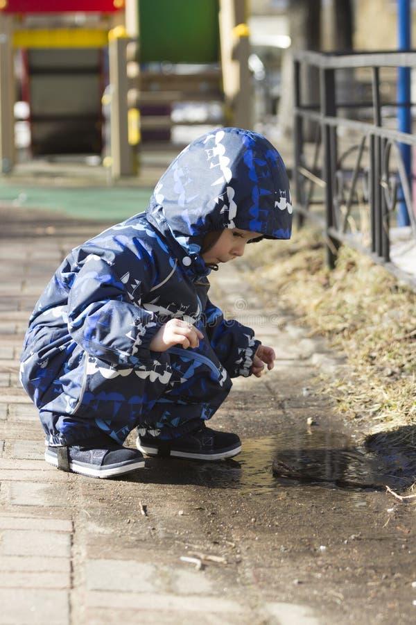En 2-årig pojke som spelar i pölen royaltyfria foton