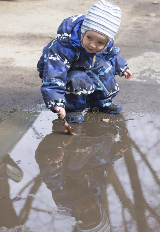 En 2-årig pojke som spelar med ett blad i en pöl arkivfoton